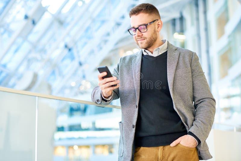 Homme d'affaires Using Phone dans l'immeuble de bureaux images stock