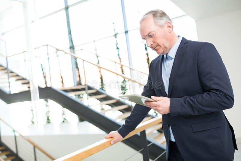 Homme d'affaires Using Tablet Computer tout en se penchant sur la clôture images stock