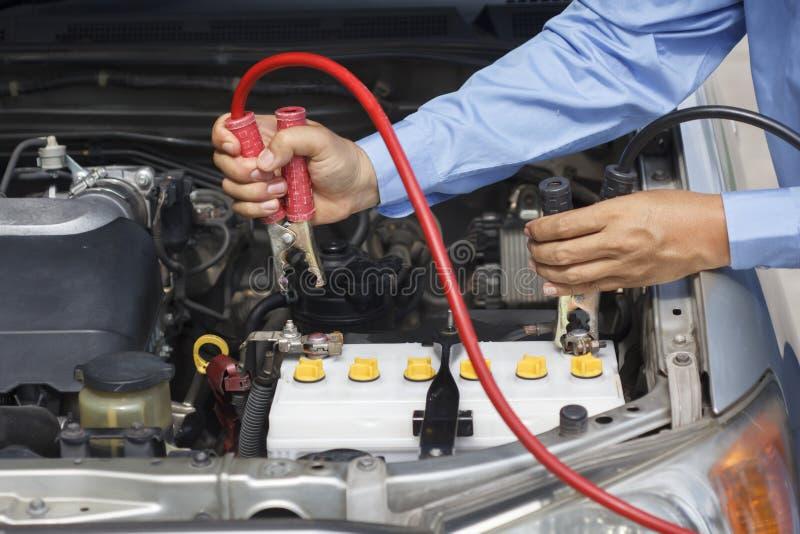 Homme d'affaires utilisant des câbles de pullover pour mettre en marche une voiture photo libre de droits
