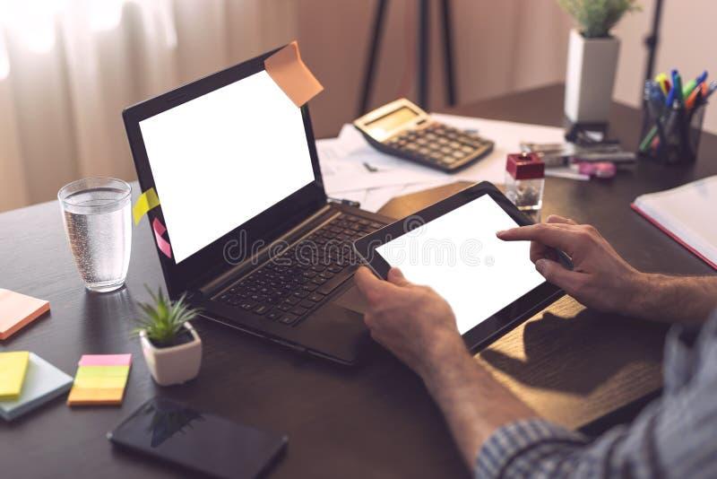Homme d'affaires utilisant l'ordinateur portable et un téléphone intelligent images libres de droits