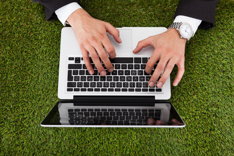 Homme d'affaires utilisant l'ordinateur portable sur l'herbe photo stock