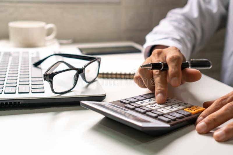 Homme d'affaires utilisant la calculatrice avec l'ordinateur portable et les verres, concept de travail d'affaires image stock