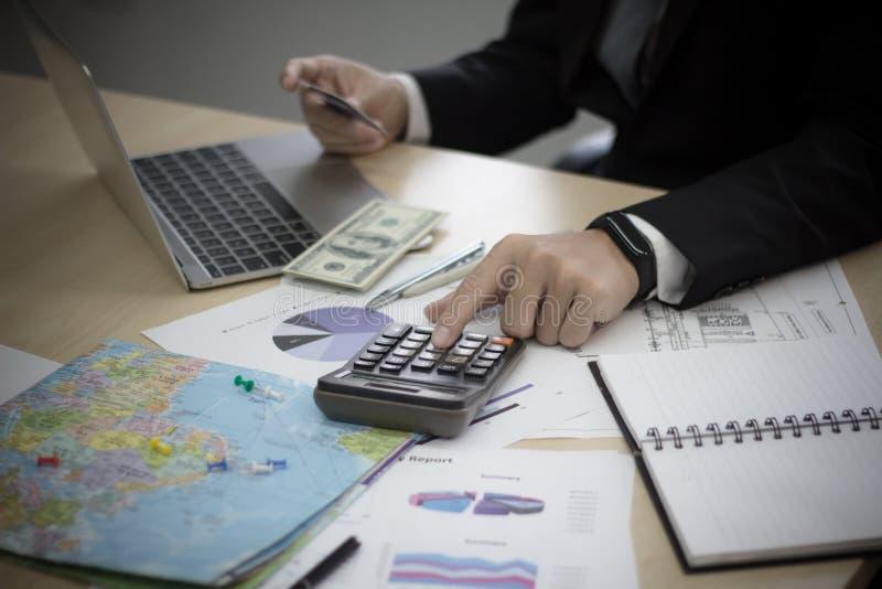 Homme d'affaires utilisant la calculatrice tenant la carte de crédit pour faire des emplettes en ligne avec l'ordinateur portable images stock