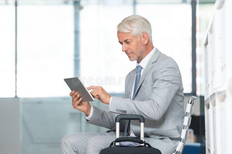 Homme d'affaires utilisant la tablette à l'aéroport image libre de droits