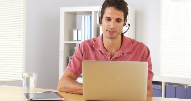 Homme d'affaires utilisant le casque à parler au téléphone photos stock
