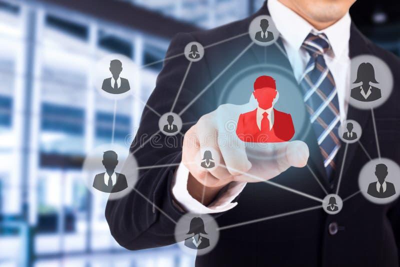 Homme d'affaires utilisant le doigt pour l'icône d'humain de contact photographie stock