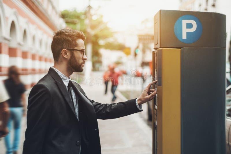 Homme d'affaires utilisant le parcomètre dehors image libre de droits