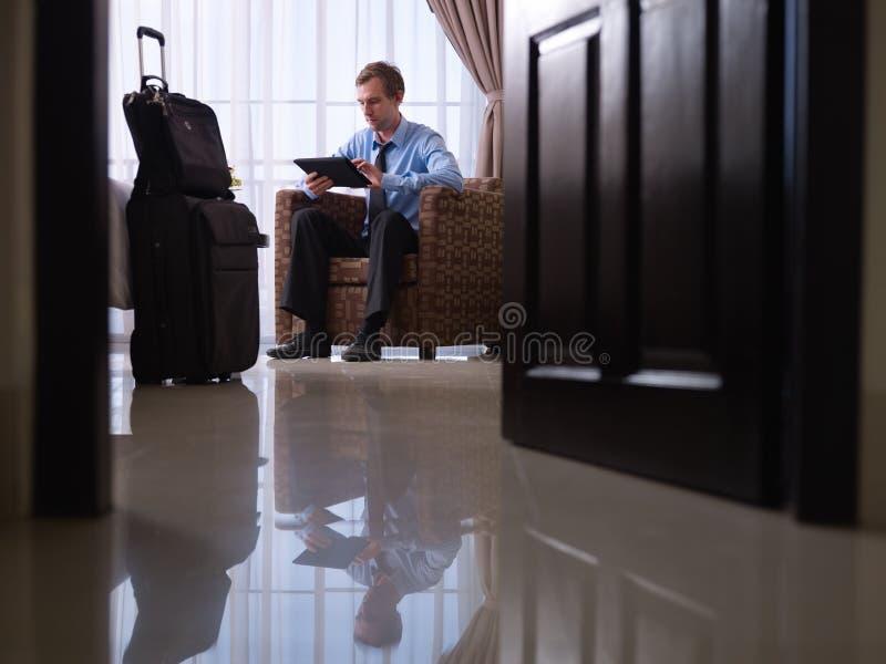Homme d'affaires utilisant le PC numérique de comprimé dans la chambre d'hôtel images stock