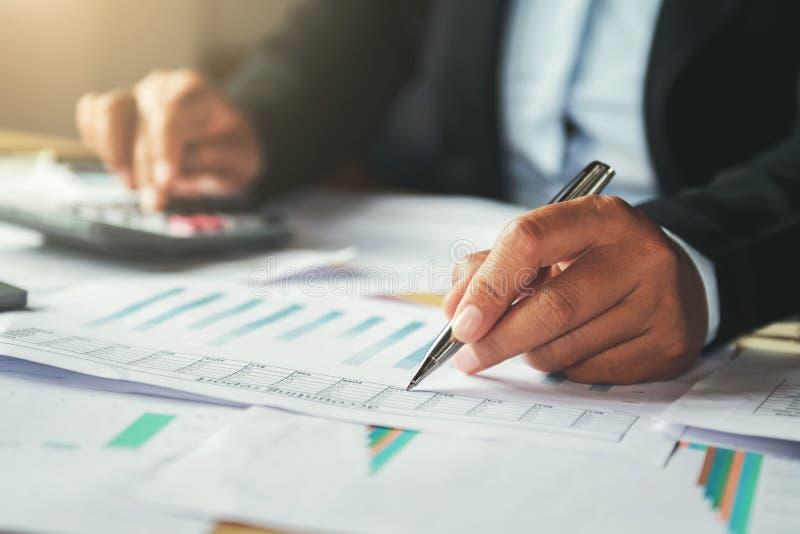 homme d'affaires utilisant le stylo et calculatrice fonctionnant dans le bureau finances images stock