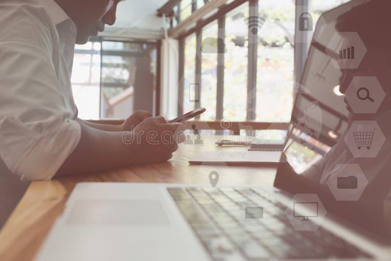 Homme d'affaires utilisant le téléphone intelligent tout en se reposant avec l'ordinateur portable sur la table photo libre de droits