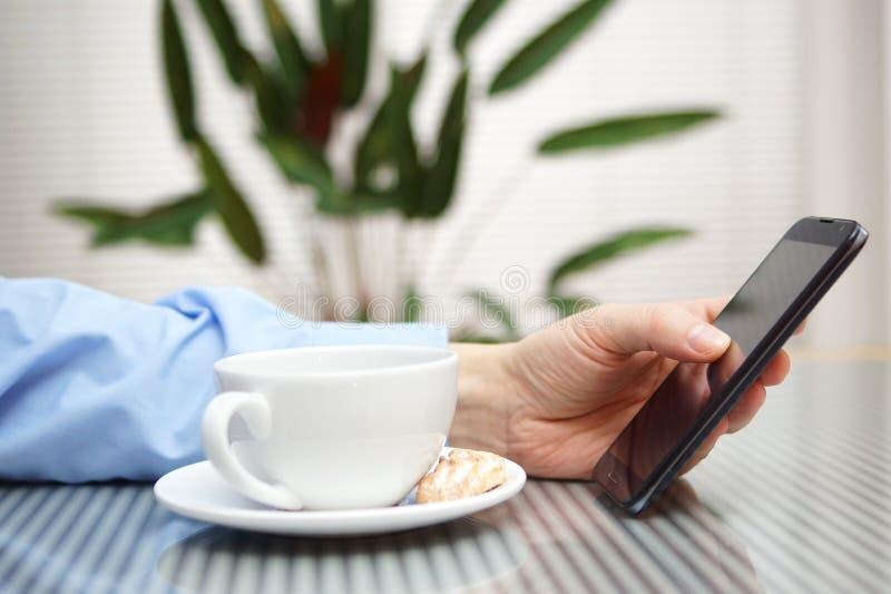 Homme d'affaires utilisant le téléphone portable et le café potable photo stock