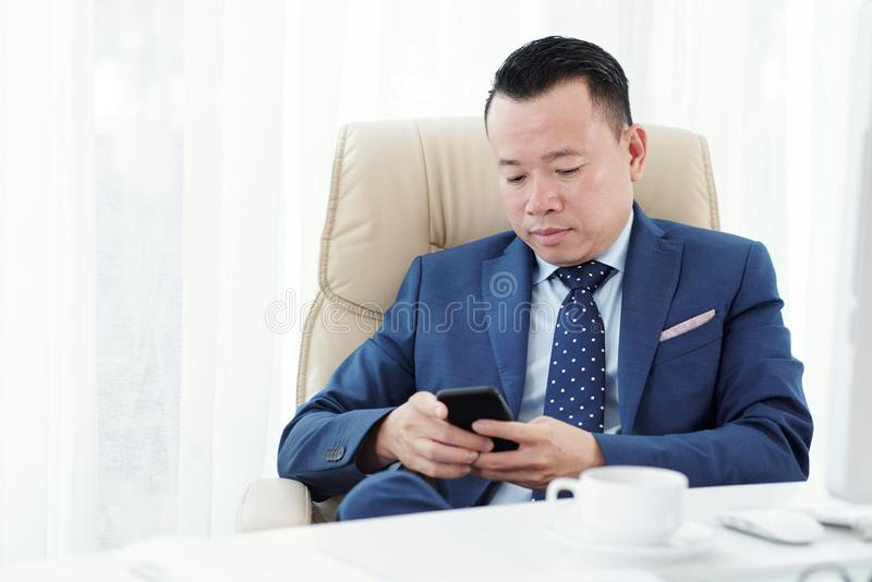 Homme d'affaires utilisant le t?l?phone portable au bureau image libre de droits
