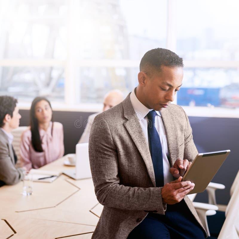 Homme d'affaires utilisant un comprimé avec trois collègues assis derrière lui photo libre de droits