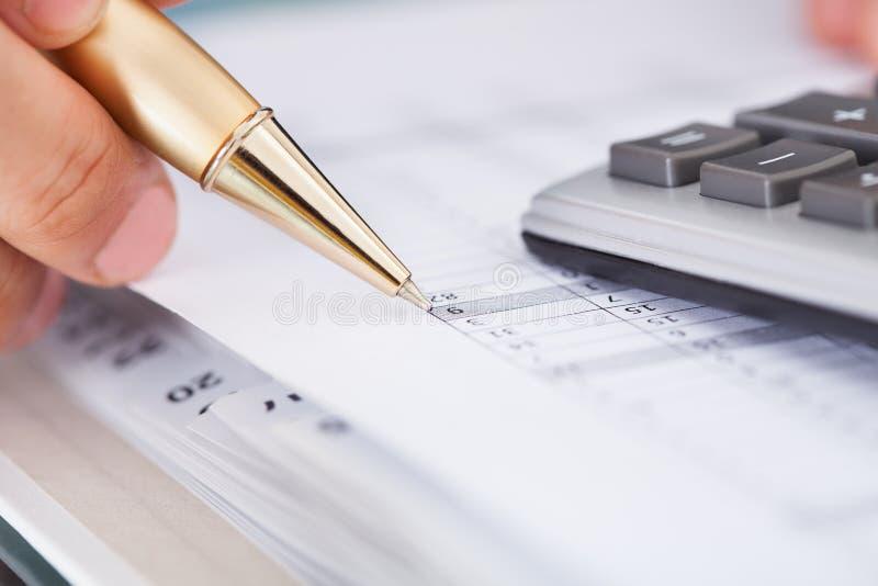 Homme d'affaires vérifiant des dépenses dans le bureau photos libres de droits