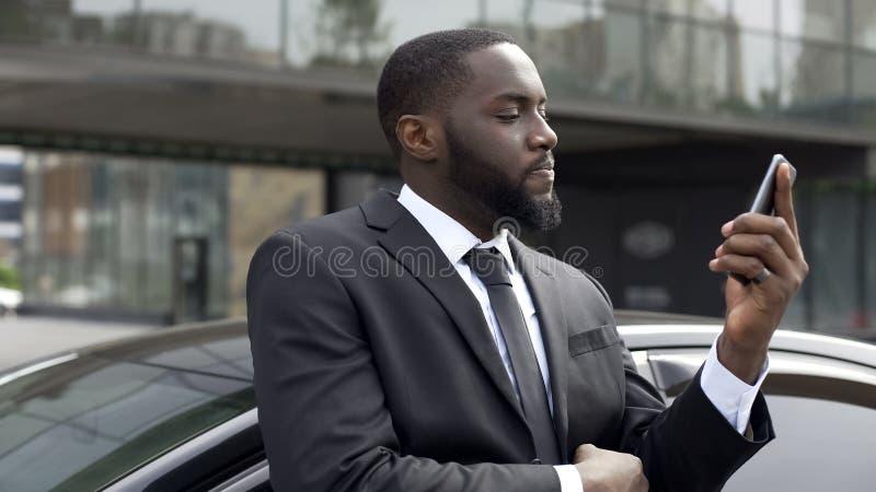 Homme d'affaires vérifiant l'équilibre APP au téléphone, contrarié avec des dépenses de wifes photo stock
