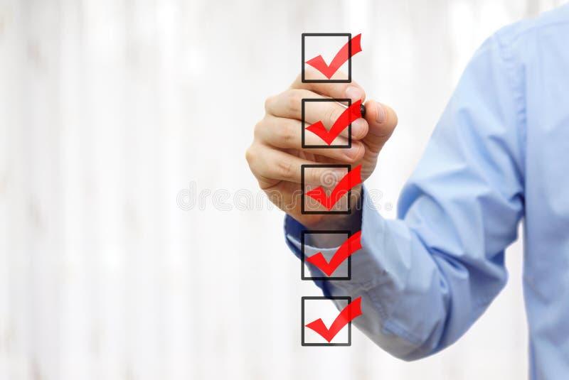 Homme d'affaires vérifiant la marque finale sur la liste de contrôle images stock