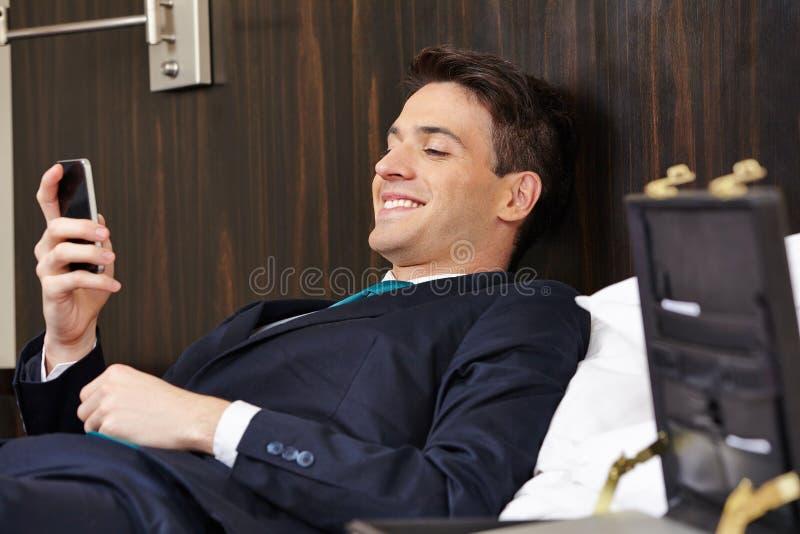 Homme d'affaires vérifiant le smartphone dans la chambre d'hôtel images libres de droits