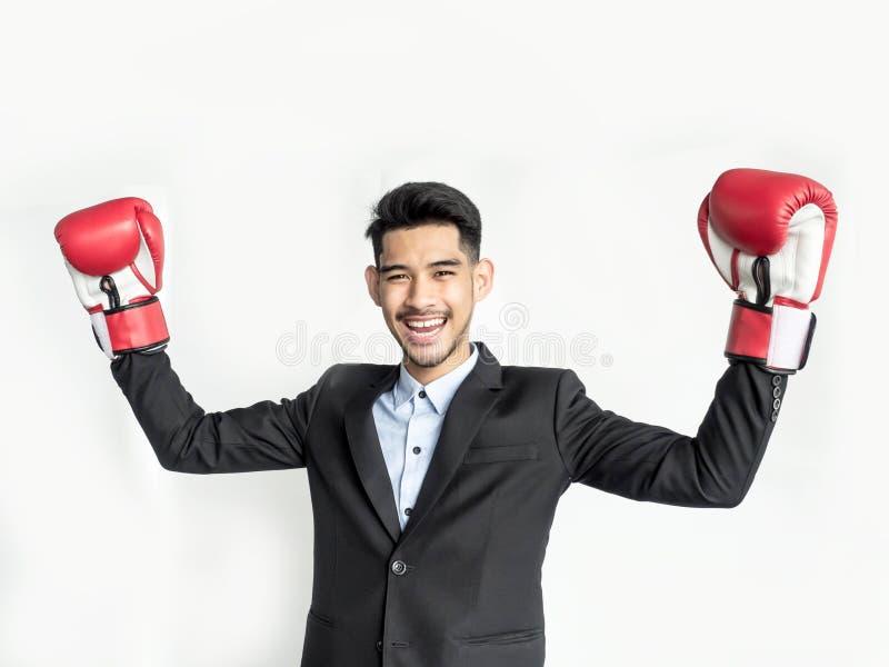 Homme d'affaires victorieux soulevant des mains avec des gants de boxe photo stock