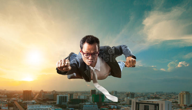 Homme d'affaires volant au-dessus du gratte-ciel pour des affaires réussies et image libre de droits