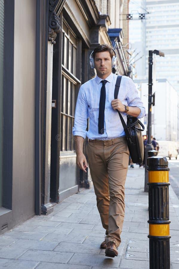 Homme d'affaires Wearing Wireless Headphones marchant pour travailler photographie stock libre de droits