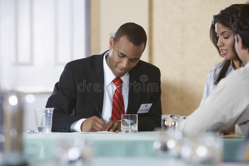 Homme d'affaires Writing On Document avec des collègues s'asseyant au bureau images libres de droits