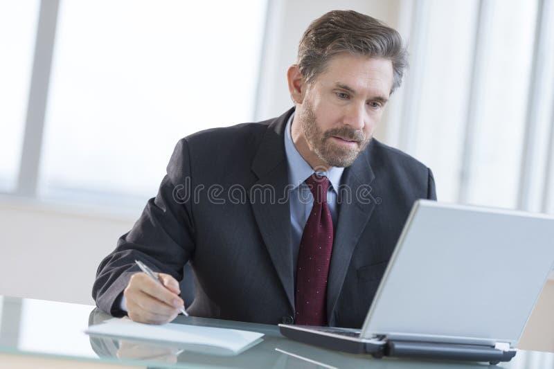 Homme d'affaires Writing Notes While à l'aide de l'ordinateur portable au bureau images libres de droits