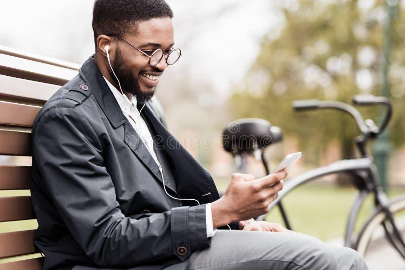 Homme d'afro-américain avec le téléphone se reposant sur le banc près de la bicyclette images stock