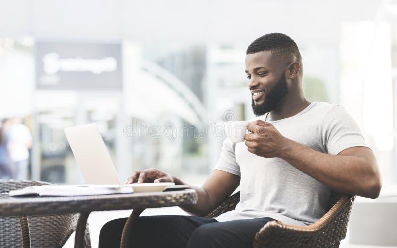 Homme d'afro-américain ayant déjeuner temps en café et à l'aide de l'ordinateur portable images stock