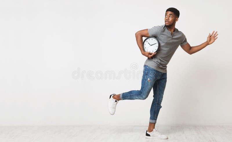 Homme d'afro-américain courant avec le grand réveil images stock