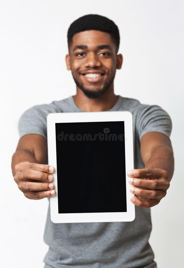 Homme d'afro-américain montrant l'écran numérique vide de comprimé photo stock