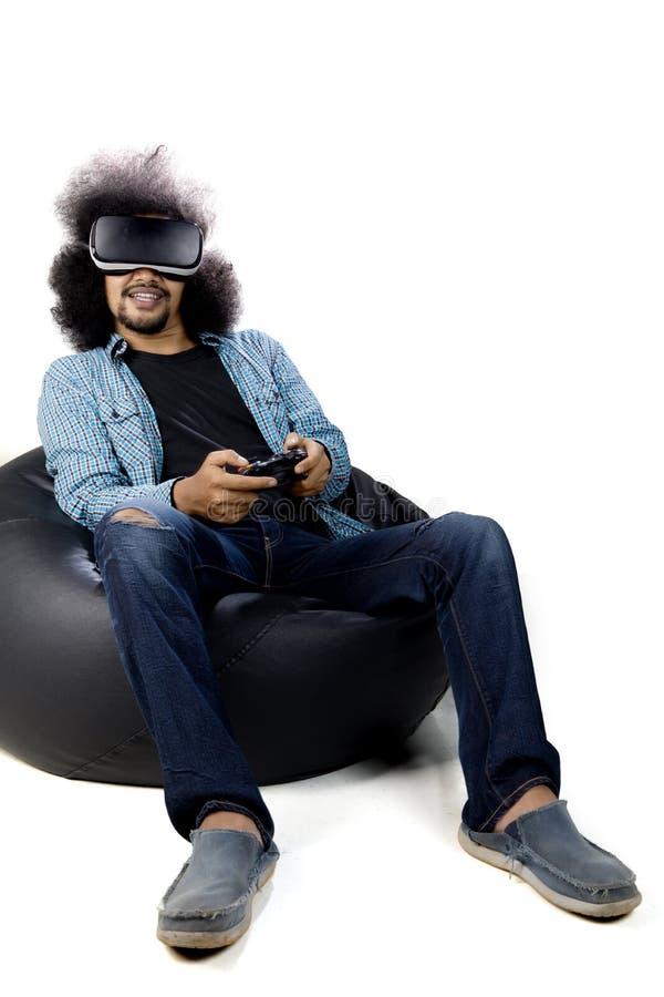 Homme d'Afro employant des verres de réalité virtuelle sur le studio image libre de droits