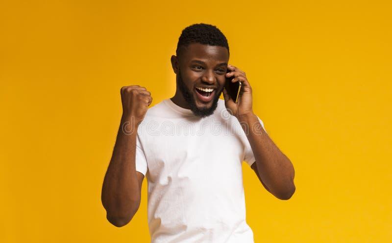 Homme d'afro-am?ricain parlant sur le t?l?phone portable et le sourire photo libre de droits