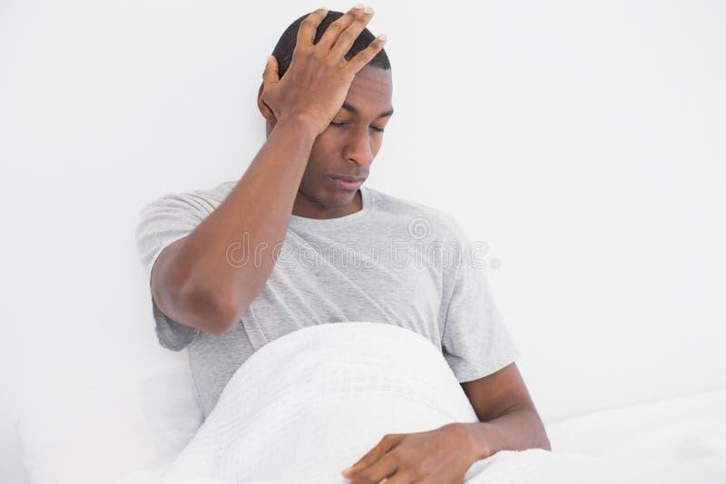 Homme d'Afro souffrant du mal de tête dans le lit images libres de droits