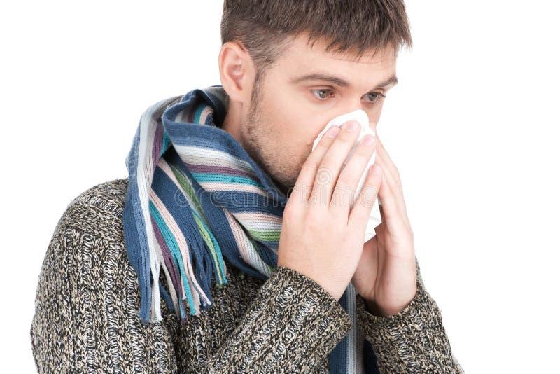 Homme d'allergie soufflant son nez en papier de soie de soie image stock