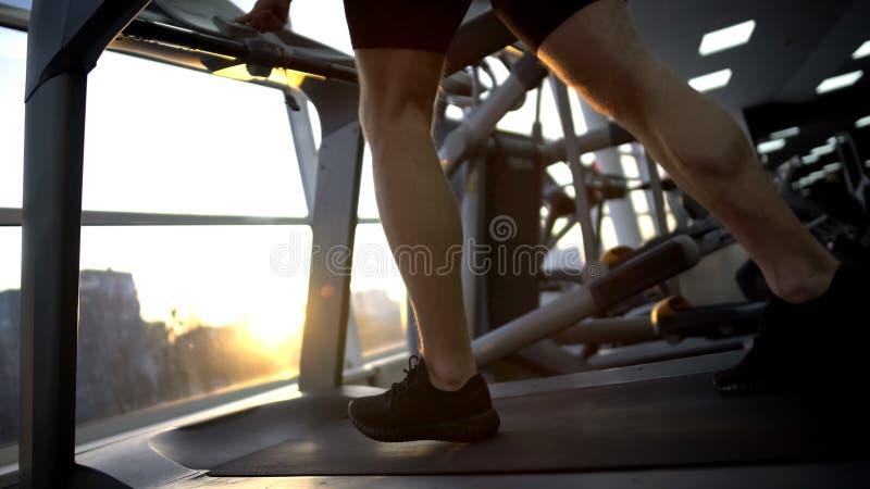 Homme d'athlète courant sur le tapis roulant dans le gymnase, réchauffant avant séance d'entraînement, santé photos libres de droits