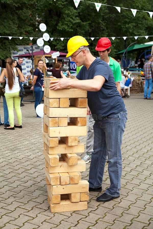 Homme d'entrepreneur jouant le jeu dehors Grande, grande, géante concurrence de jenga images stock
