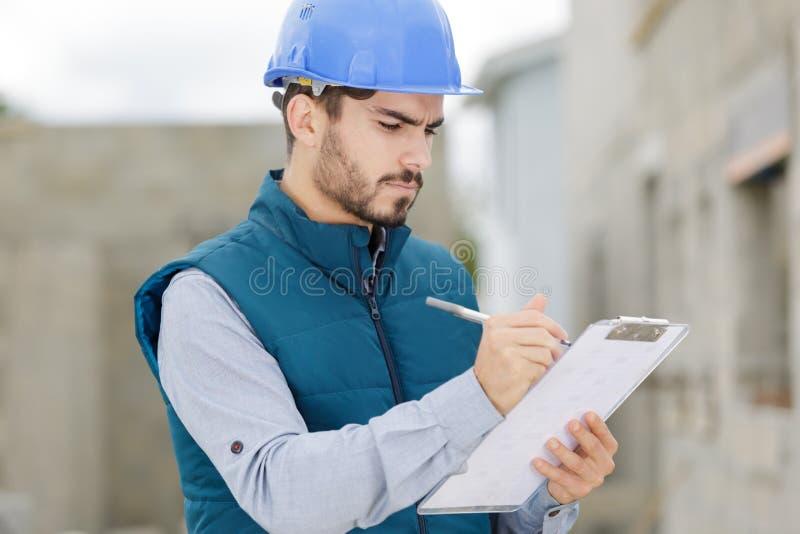 Homme d'ingénieur prenant des notes sur le presse-papiers photographie stock libre de droits