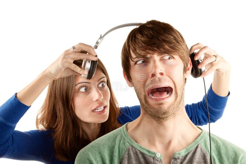 Homme d'interupts de femme avec des écouteurs images libres de droits
