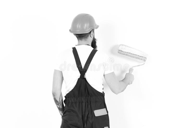 Homme d'isolement sur le fond blanc Concept à la maison de rénovation Tournez de retour le mur de peinture de constructeur avec l photo libre de droits