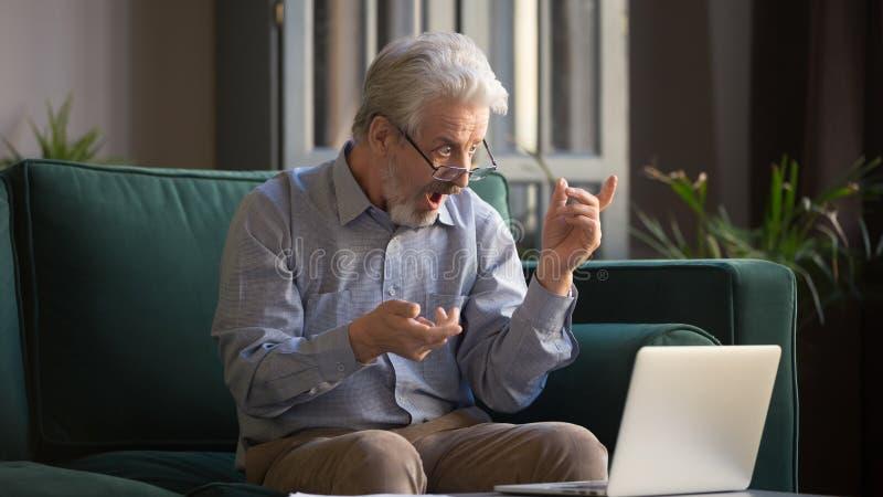 Homme d'une chevelure gris excité étonné par des nouvelles incroyables sur l'ordinateur portable photographie stock