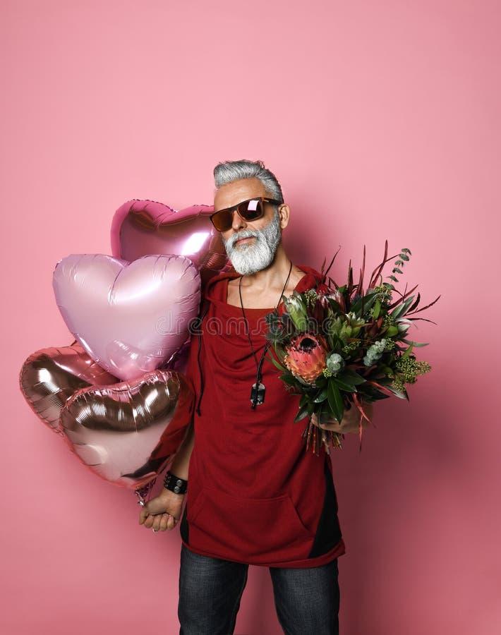 Homme d'une cinquantaine d'années barbu avec des ballons et des fleurs images libres de droits