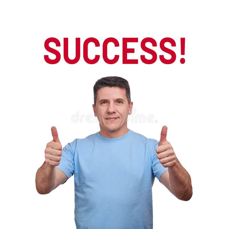 Homme d'une cinquantaine d'années bel avec un léger sourire, montrant des pouces avec deux mains et succès de mot photos stock