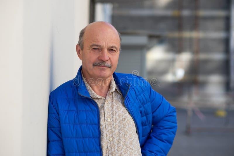 Homme d'une cinquantaine d'années bel posant dans la veste bleue se penchant le mur gris Verticale mâle extérieure photographie stock