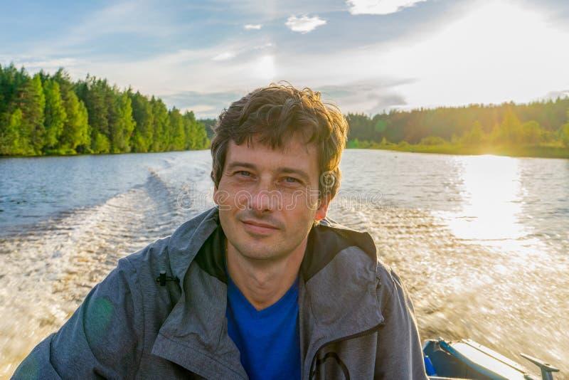 Homme d'une cinquantaine d'années bel s'asseyant au bateau sévère et flottant le long de la rivière du nord sur le beau fond de p photographie stock libre de droits