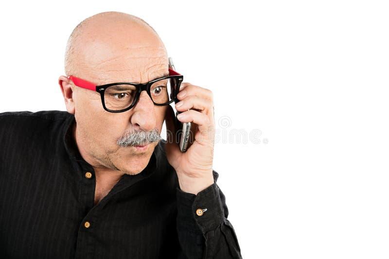 Homme d'une cinquantaine d'années étonné parlant sur son mobile photographie stock libre de droits