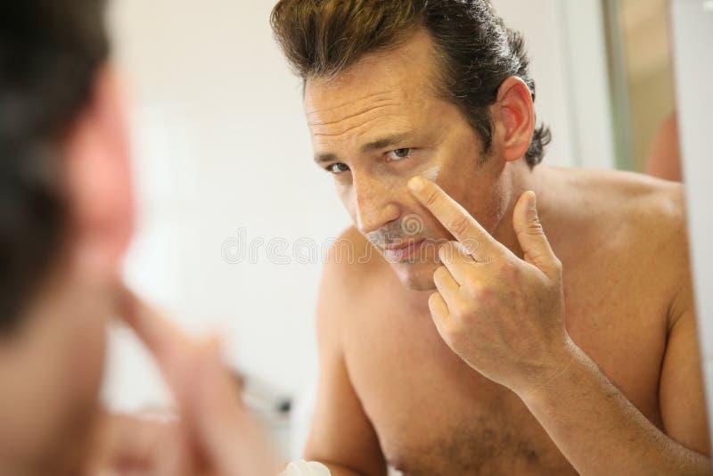 Homme d'une cinquantaine d'années appliquant une lotion sur son visage photos stock