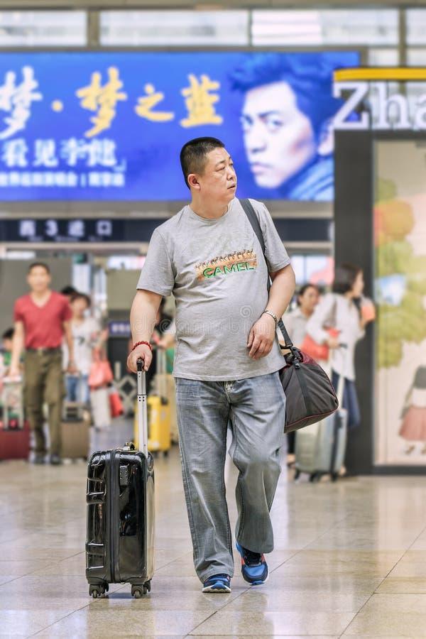Homme d'une cinquantaine d'années avec la valise aux sud de gare ferroviaire de Pékin, Chine photos libres de droits