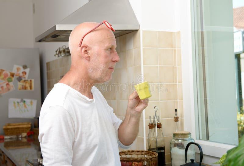 Homme d'une cinquantaine d'années buvant une tasse de café photos stock