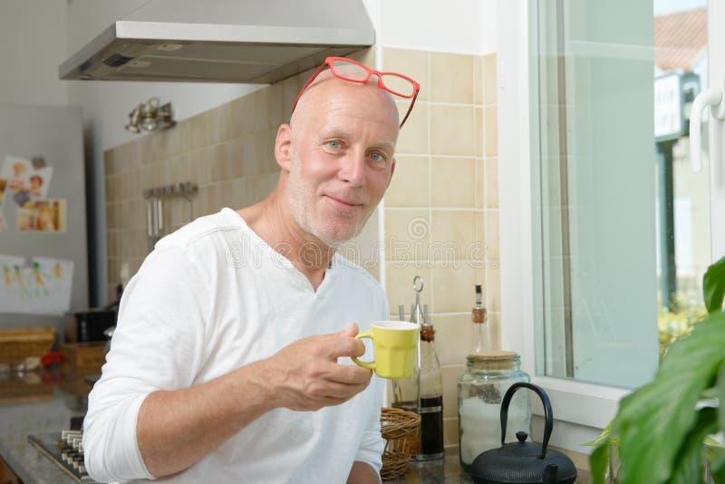 Homme d'une cinquantaine d'années buvant une tasse de café image stock