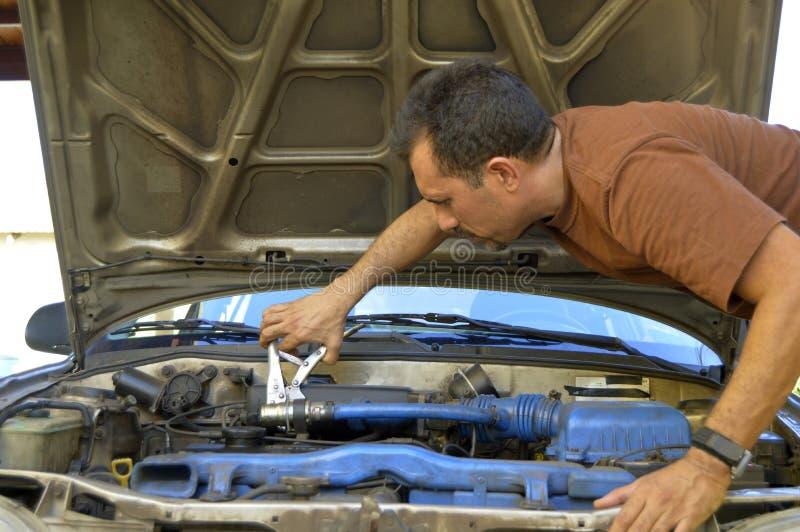Homme d'une cinquantaine d'années essayant de réparer leurs propres voitures photographie stock libre de droits